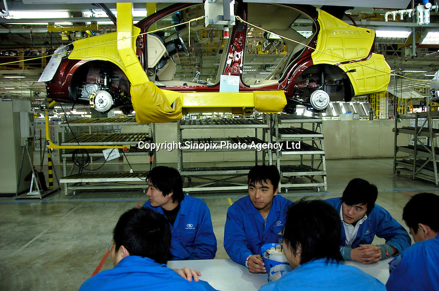 Workers of Shanghai GM Dong Yue Motors Company Limited, take a 15-minute break at the assembly line of GM Chevrolet Sail, in Yantai, Shandong province, China. .03 Jan 2007