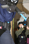 Women police officers in training holding a paint ball simulated gun clearing a stairwell in a school shooting scenario