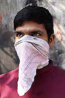 A worker stands in a small informal leather factory. The dust produced from the manufacturing of products is damaging to the worker's health health hence they try to protect themselves with basic face scarves.