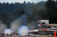 Aug. 6, 2011; Kent, WA, USA; NHRA funny car driver Brian Thiel (right) burns out alongside Melanie Troxel during qualifying for the Northwest Nationals at Pacific Raceways. Mandatory Credit: Mark J. Rebilas-