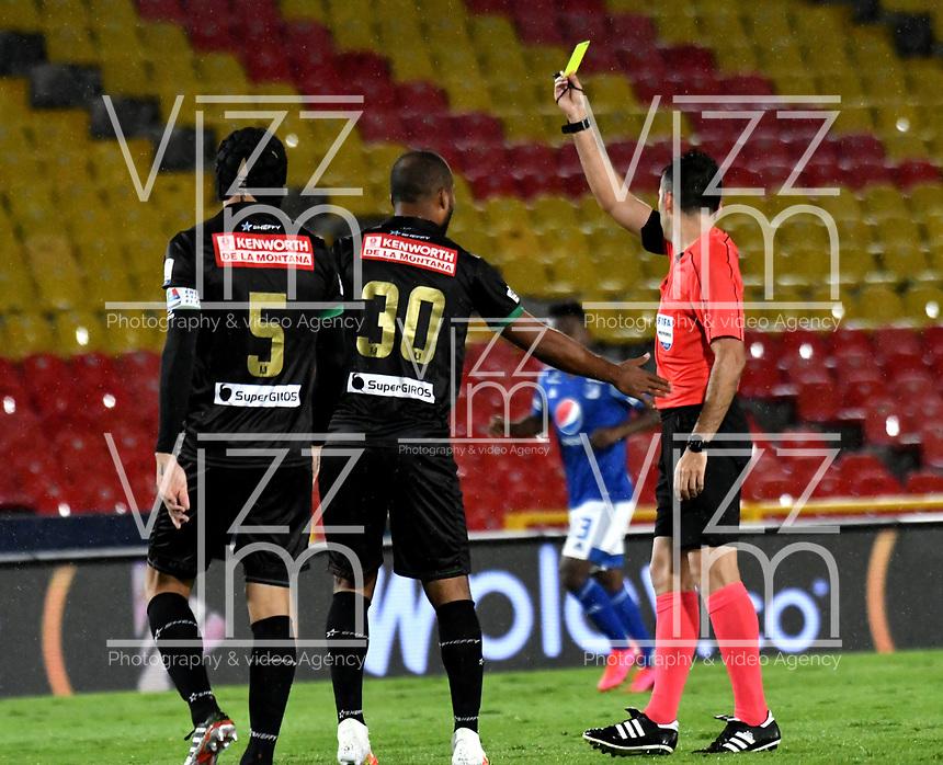 BOGOTA-COLOMBIA, 19-09-2020: Carlos Betancur, arbitro muestra tarjeta amarilla a Luis Payares de Once Caldas, durante partido entre Millonarios y Once Caldas de la fecha 9 por la Liga BetPlay DIMAYOR I 2020 jugado en el estadio Nemesio Camacho El Campin de la ciudad de Bogota. / Carlos Betancur, referee shows yellow card to Luis Payares of Once Caldas, during a match between Millonarios and Once Caldas of the 9th date for the BetPlay DIMAYOR Leguaje I 2020 played at the Nemesio Camacho El Campin Stadium in Bogota city. / Photo: VizzorImage / Luis Ramirez / Staff.