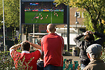 Welsh rugby supporters watching the closing stages of the RWC semi-final with France this morning, which they lost. They watched the match on a large outside television screen in Castle Square in the centre of Swansea..