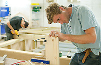 Using a coping saw to prepare a window frame.   Able Skills in Dartford, Kent, runs courses in construction industry skills like, bricklaying, carpentry and tiling.