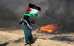 A Palestinian woman waves the national flag during clashes with Israeli security forces in tents protest where Palestinians demanding the right to return to their homeland, at the Israel-Gaza border, in Khan Younis in the southern Gaza Strip, on May 11, 2018. Photo by Ashraf Amra
