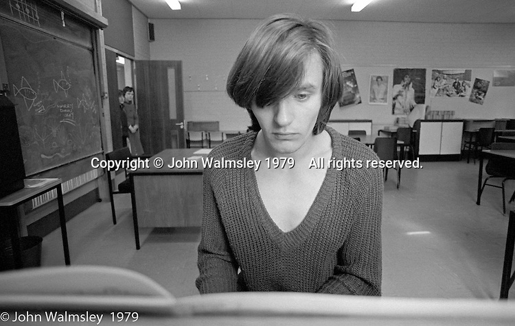 A recent ex-student comes back to help out and play the piano, the Education Centre, Wester Hailes, Scotland, 1979.  John Walmsley was Photographer in Residence at the Education Centre for three weeks in 1979.  The Education Centre was, at the time, Scotland's largest purpose built community High School open all day every day for all ages from primary to adults.  The town of Wester Hailes, a few miles to the south west of Edinburgh, was built in the early 1970s mostly of blocks of flats and high rises.