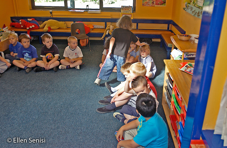 MR / Abingdon, Oxfordshire, England.Thomas Reade Primary School.Foundation Class for ages 3-5 .Boy walks around circle of students, tapping them on the head, during classroom game..(Ages 3-4 attend this class half-day, age 5 attends full-day).©Ellen B. Senisi