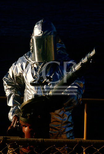 Rio de Janeiro, Brazil. Oil rig worker in silver fireproof suit and helmet with visor with water cannon fire hose.