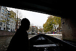 A woman silhouetted while riding in a boat through the canals of Amsterdam, the Netherlands.