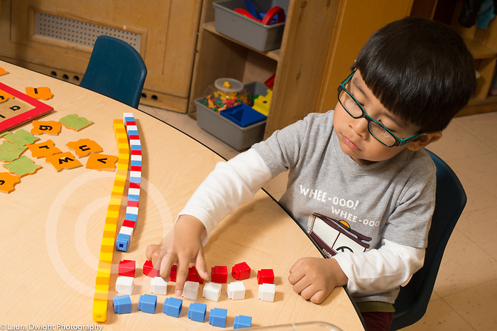 Education preschool 3-4 year olds boy using manipulatives counting colored cubes after making patterned towers