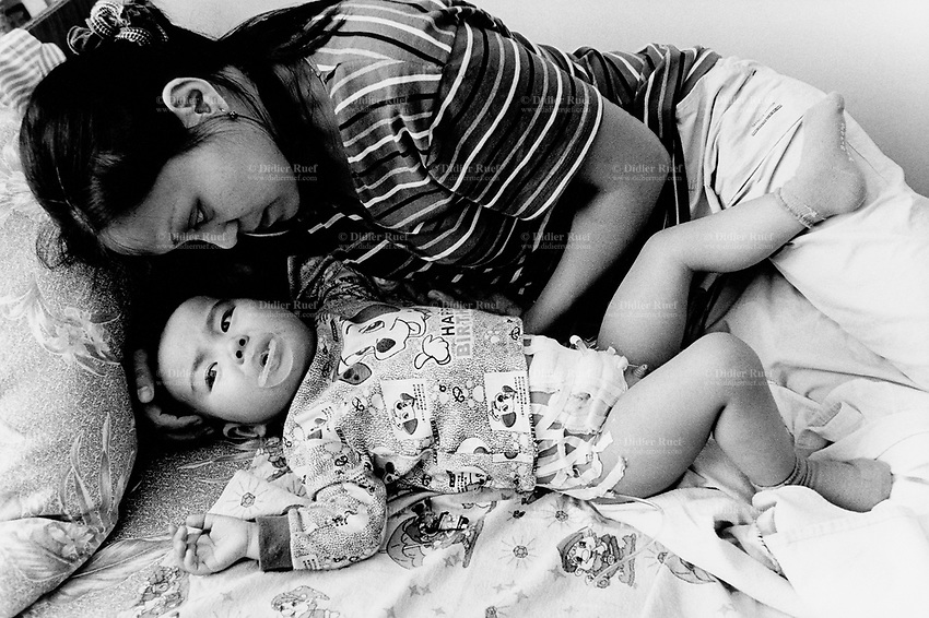 Kazakhstan. Semipalatinsk. Regional Children Clinical Hospital. Mother and daughter on a bed. The child suffers from an urology disease. She was born in 2005 near the Semipalatinsk Polygon ( called today National Nuclear Center of Kazakhstan). The girl is a second (or third) generation victim of the 456 atomic testing - 116 atmospheric, 340 underground - from 1949 to 1989. The regions high frequency of urology diseases is primarily due to fallout from nearby nuclear test sites. The child shows the human and environmental effects of nuclear radiation, contamination and pollution from atomic tests programs of the former Soviet Union. Semey is the Kazakh name for Semipalatinsk and is located in the Eastern Kazakhstan Province. © 2008 Didier Ruef.