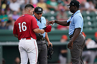 Umpires Ray Valero, left, and James Jean inspect the hat and glove of pitcher Yusniel Padron_Atriles (16) during a game between the Greensboro Grasshoppers and the Greenville Drive on Saturday, July 24, 2021, at Fluor Field at the West End in Greenville, South Carolina. (Tom Priddy/Four Seam Images)