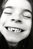 Boy (5-7) smiling, close-up (focus on mouth, B&W)