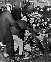 1969 FILE PHOTO - ARCHIVES -<br /> <br /> A woman chained to other militant feminists is grabbed by a Montreal policeman during a protest last night against the city's anti-demonstration bylaw. Today police patrolled the Grey Cup parade's route to avert more trouble.<br /> <br /> 1969<br /> <br /> PHOTO :  Doug Griffin - Toronto Star Archives - AQP