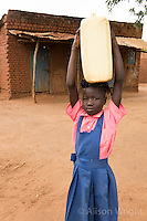 N. Uganda, Kitgum District. School girl carrying water to her home.