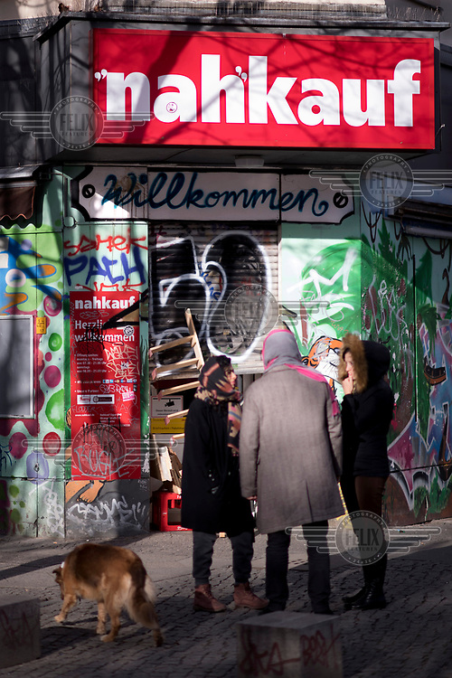 People gathered outside Nahkauf, a graffiti covered shop in Kreuzberg, a district undergoing significant redevelopment and gentrification.