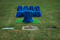 Four blue fabric draped chairs and podium on an artificial grass run sit ready for a family memorial service at a cemetery.