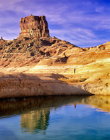 Hiker near reflection pool on banks of Lake Powell, Utah