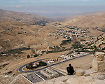 Overlook.  A young man perches right on the edge of Karak Castle's battlements, atop a sheer face several hundred feet above the Wadi al-Karak, below.  The bluffs on the Israeli side of the Dead Sea are clearly visible in the distance.  According to legend, the ancient Biblical condemned cities of Sodom and Gomorrah were between Karak and the Dead Sea, in this view.  The Crusader castle at Karak guarded the eastern border of the Kingdom of Jerusalem after the first Crusade. © Rick Collier