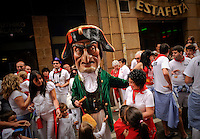 People greet a man dressed as a giant during the giants and big heads parade of the San Fermin festival, on July 10, 2012, in the Northern Spanish city of Pamplona. The festival is a symbol of Spanish culture that attracts thousands of tourists to watch the bull runs despite heavy condemnation from animal rights groups. (c) Pedro ARMESTRE