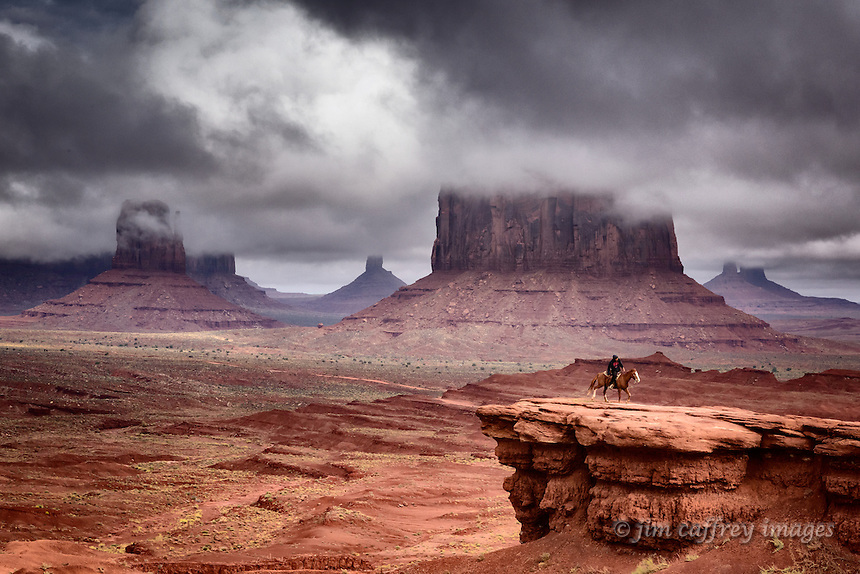 A lone riderin Monument Valley with low hanging clouds partially obscuring the Mitten and Merrick Butte