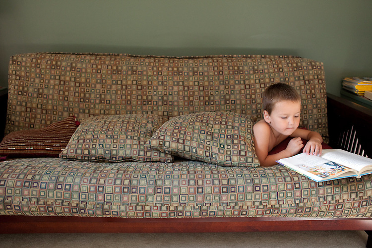 My younger son buried himself under couch cushions to read in our living room.