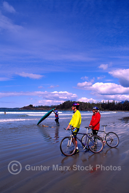 West Coast, Vancouver Island, BC, British Columbia, Canada - Young Couple mountain biking on Beach near Tofino, Summer - Cyclists are Model Released