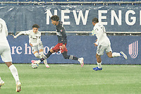 FOXBOROUGH, MA - NOVEMBER 1: Kevin Paredes #30 of DC United comes in to tackle Tajon Buchanan #17 of New England Revolution during a game between D.C. United and New England Revolution at Gillette Stadium on November 1, 2020 in Foxborough, Massachusetts.