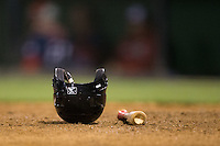 A baseball bat and batting helmet sit on the dirt near home plate during the South Atlantic League game between the Hagerstown Suns and the Kannapolis Intimidators at Kannapolis Intimidators Stadium on May 4, 2016 in Kannapolis, North Carolina.  The Intimidators defeated the Suns 7-4.  (Brian Westerholt/Four Seam Images)