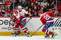 WASHINGTON, DC - JANUARY 31: Jonas Siegenthaler #34 of the Washington Capitals checks Mathew Barzal #13 of the New York Islanders into the boards as Lars Eller #20   controls the puck during a game between New York Islanders and Washington Capitals at Capital One Arena on January 31, 2020 in Washington, DC.