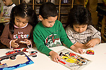 Education preschoool children ages 3-5 girl and two boys working on wooden puzzles horizontal