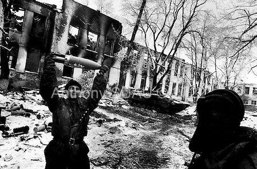 Grozny, Chechyna.January 1995.On the front line a young Russian soldier plays with an unexploded tank shell laying amongst the ammunition that is not yet used. The building behind him is the former hospital.
