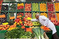 Berlino, fruttivendolo dispone frutta e verdura nelle cassette. Molti prodotti sono di esportazione italiana: mele Royal Gala, zucchine, pesche e melanzane --- Berlin, greengrocer placing fruit and vegetables in the boxes. Many products of Italian export: Royal Gala apples, zucchini, eggplant, peaches