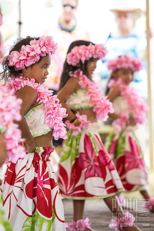 Girls wearing pink plumeria lei and haku head lei perform a hula in Hale'iwa, North Shore, O'ahu.