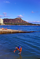 A young man jumps into the ocean from an area known as Kapahulu Groin at Kuhio Beach Park in Waikiki, with Diamond Head in the background.