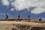 Group of hikers walking on slickrock sandstone in Arches National Park, Utah, USA. .  John offers private photo tours in Arches National Park and throughout Utah and Colorado. Year-round.