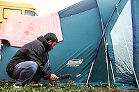 Pictured: A man removes mud from outside his tent Tuesday 08 March 2016<br /> Re: Heavy overnight rain has flooded the migrant camp at the Greek FYRO Macedonian border of Idomeni in Greece
