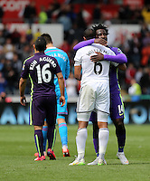 SWANSEA, WALES - MAY 17: Ashley Williams of Swansea (C) is embraced by Wilfried Bony of Manchester City after the Premier League match between Swansea City and Manchester City at The Liberty Stadium on May 17, 2015 in Swansea, Wales. (photo by Athena Pictures/Getty Images)