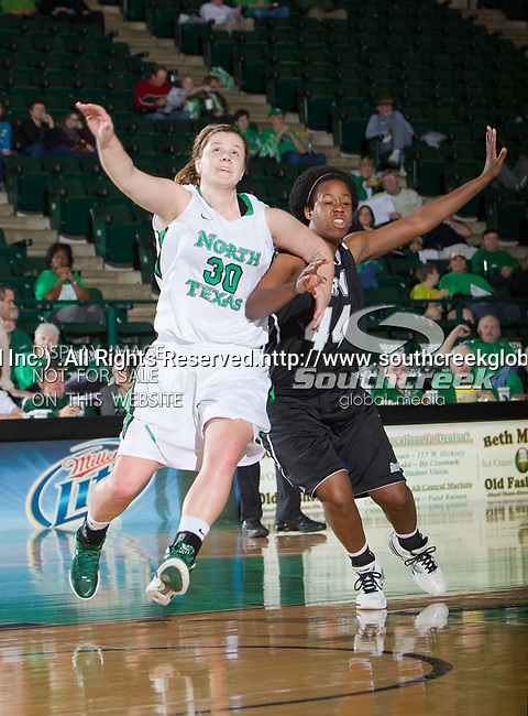North Texas Mean Green forward Sara Stanley (30) and Troy Trojans forward Tenia Manuel (44) in action during the game between the Troy Trojans and the University of North Texas Mean Green at the North Texas Coliseum,the Super Pit, in Denton, Texas. UNT defeats Troy 57 to 36.