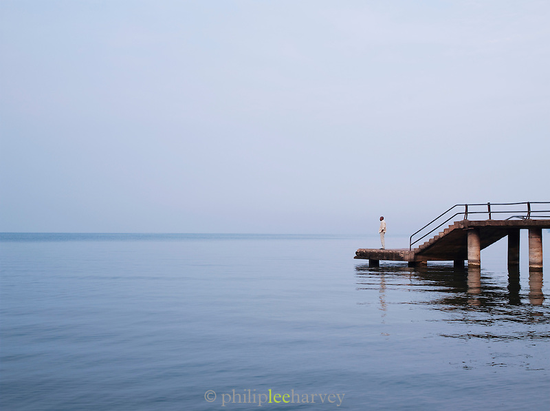 Man standing on a dock looking out into the mist of Lake Kivu, near Gisenyi, Rwanda