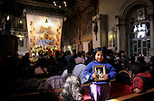 Paucartambo, Peru. Small girl holding a picture of the Virgin of Carmen in the church before the procession.
