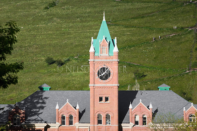 Main Hall on the University of Montana campus in Missoula, Montana. People walking the trail to the M on Mount Sentinel