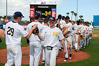 Michigan Wolverines Miles Lewis (3) high fives teammates, including Blake Beers (29), with Jonathan Engelmann (2) and Christan Bullock (5) following, after a game against Army West Point on February 18, 2018 at Tradition Field in St. Lucie, Florida.  Michigan defeated Army 7-3.  (Mike Janes/Four Seam Images)