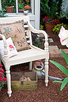 Cute chair for relaxing in the garden, with rustic watering can, amaryliis in pot container, house, rustic wooden box.