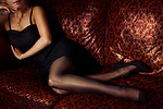 Closeup of legs of a sexy woman lying on a couch wearing a short black dress, black stockings and high heel shoes Image © MaximImages, License at https://www.maximimages.com