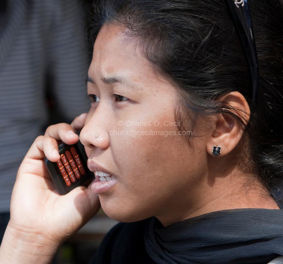 Kathmandu, Nepal.  Young Nepalese Woman Using Cell Phone.  Note diamond nose-pin.