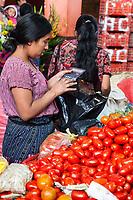 Chichicastenango, Guatemala.  Tomato Vendor Calculating Price of a Sale in the Indoor Market.  Quiche (K'iche') Ethnic Group.