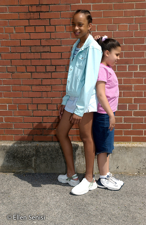 MR / Schenectady, NY. Yates Arts in Education Magnet School / urban public elementary school / Grade 5.Similar-age friends and classmates outside on playground compare height.  Their size disparity reflects normal differences in growth and maturity (Girl left:11, African-American; Girl right: 10, Puerto-Rican American)..MR: AD-g5a Bla6 Mel12..© Ellen B. Senisi