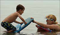A young boy (model released) and his mother (model released) play while at the beach on the Atlantic ocean. Photo taken on Sullivan's Island, near Charleston, South Carolina beach on the Atlantic Ocean, but could represent a beach scene anywhere.