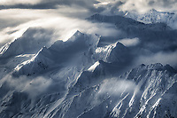 The jagged icy peaks of Alaska's Chugach Mountains emerge from the clouds, photographed from high above.