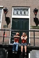 AMSTERDAM-HOLANDA-  Una pareja de muejres sentadas en un balcón durante el día de la Reina./ couple of young women sitting on a balcony during the Queen's day. Photo: VizzorImage/STR